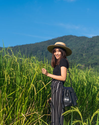 Woman in rice field Asian  Thailand Blue Sky Travel One Person Plant Hat Field Young Adult Land Nature Smiling Growth Landscape Real People Lifestyles Casual Clothing Beauty In Nature Sky Day Adult Leisure Activity Young Women Outdoors Sun Hat