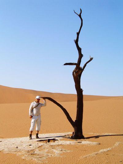 Full length of man standing by bare tree on desert against clear sky