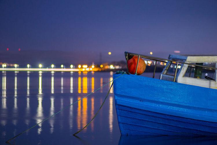 Illuminated bridge over sea against clear sky at night