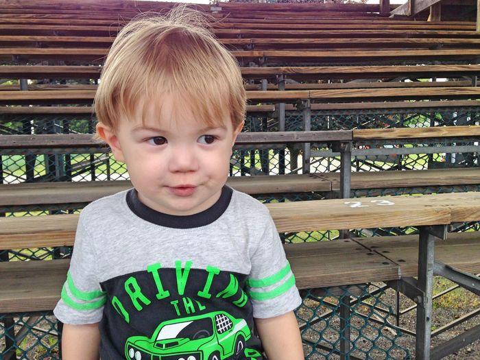 Boy Sitting On Bleacher At Stadium