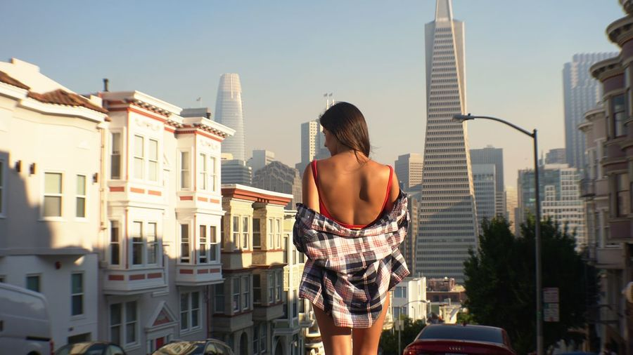Rear view of woman standing against buildings in city