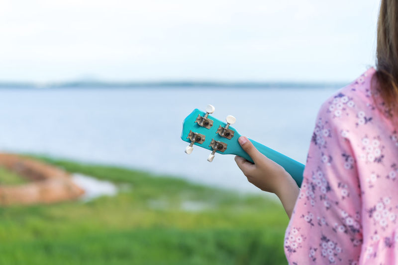 Young woman playing ukulele against lake and sky