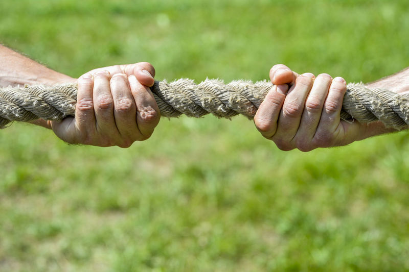 Close-up of hands holding rope on field
