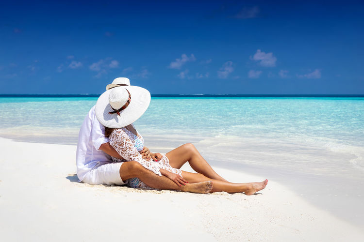 Romantic couple in white summer clothes lies on a tropical beach and enjoys the vacation Beach Sea Land Hat Water Full Length Sky One Person Real People Relaxation Leisure Activity Holiday Vacations Sand Trip Lifestyles Sitting Beauty In Nature Horizon Over Water Sun Hat Outdoors Turquoise Colored Man Woman Couple Love Hugging Honeymoon Maldives Caribbean Togetherness Elegant White Fashion Turquoise Colored Ocean Shore Lagoon Island Travel