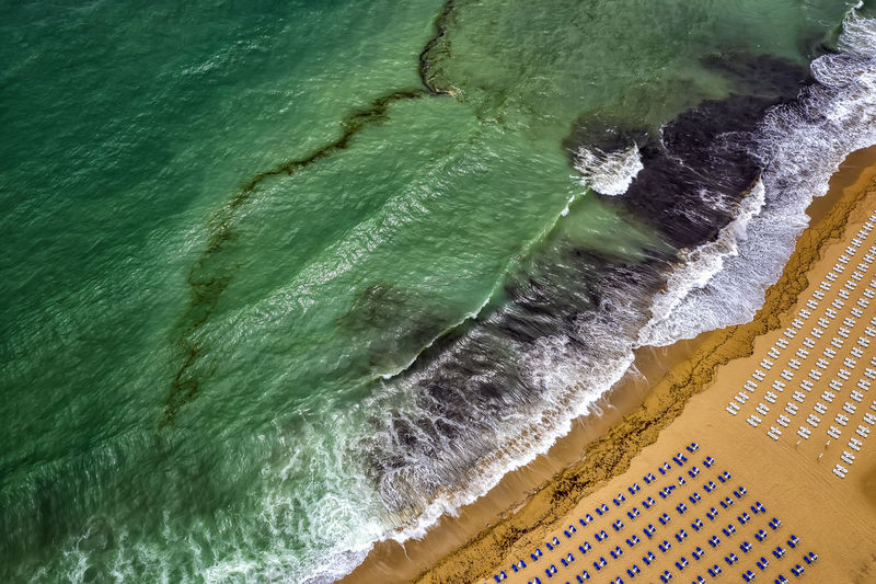 Aerial view of an amazing beach with white umbrellas, lounge chair, and turquoise sea. Tropical sea beach coastline, summer holiday. Drone  Dronephotography Drone Photography Scenics Natore Beach Beachphotography Aerial View Aerial Aerial Photography Top Wave Sea Seascape Ocean Coast Coastline Aerial Shot Seasonal Summer Amazing View Background Panoramic