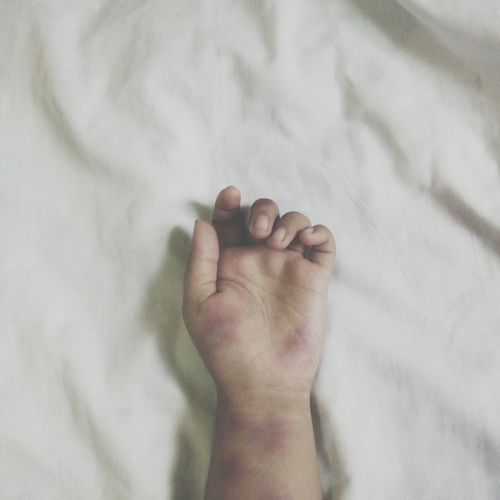 Cropped hand of woman on bed