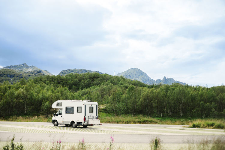 Motor home on road by mountain against sky