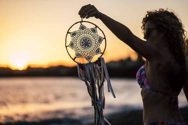 Woman holding dreamcatcher at beach against sky during sunset