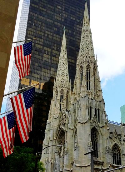 Highrise Skyscraper Old And New Architecture 5th Avenue, NYC Red White And Blue American History Blue Sky History Patriotism Flag Religion Sky Architecture Building Exterior Built Structure Stars And Stripes Place Of Worship American Flag Christianity Steeple Spirituality Cathedral National Icon Catholicism
