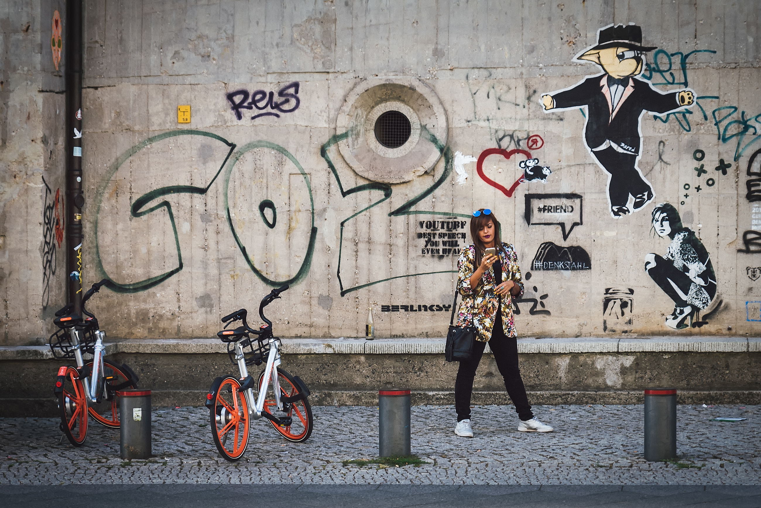 transportation, full length, bicycle, graffiti, architecture, mode of transportation, city, one person, casual clothing, creativity, real people, wall - building feature, young adult, leisure activity, building exterior, art and craft, lifestyles, built structure, street, outdoors
