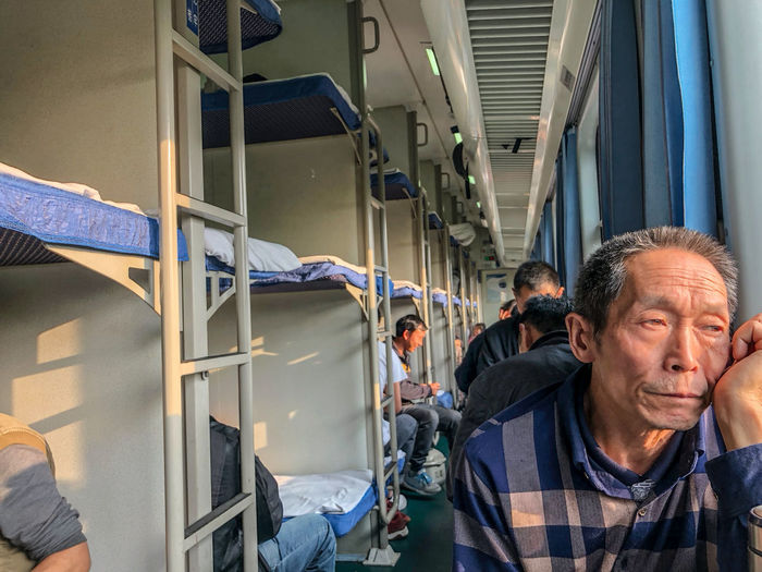 On the overnight train from Kunming to Chengdu, China, just before sunset. Mature Men Public Transportation Rail Transportation Senior Adult Train Transportation Travel Vehicle Interior