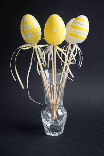Studio Shot Indoors  Black Background No People Still Life Close-up Yellow Creativity Transparent Glass - Material Vase Glass Easter Egg Eggs Easter Eggs Ribbon Bow Decoration Holidays