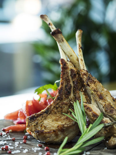 Close-up of lamb chop with rosemary on cutting board