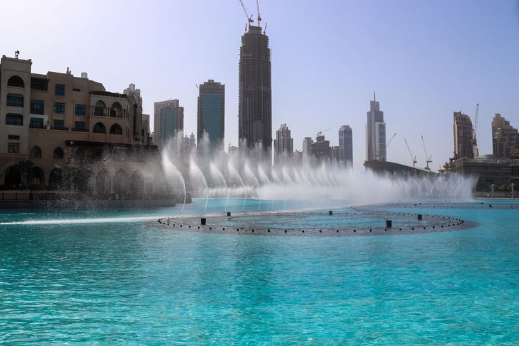 View of fountain in sea against buildings