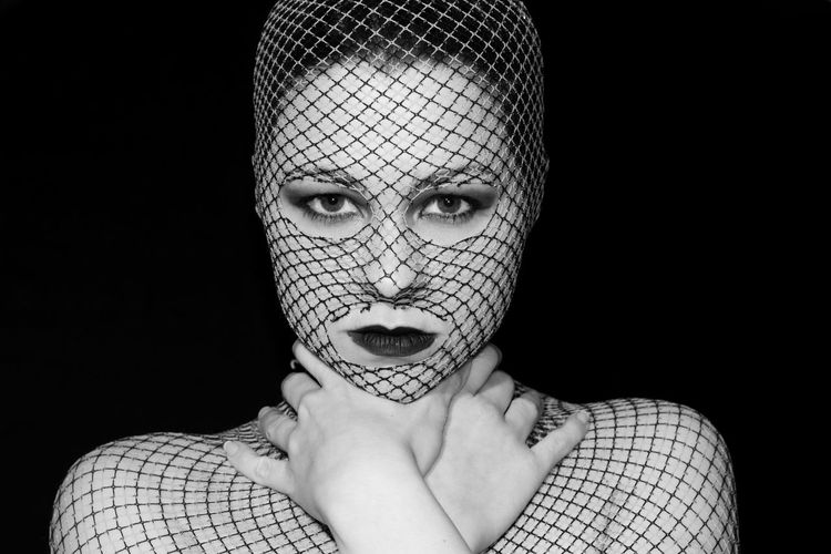 Portrait of young woman covered with net against black background