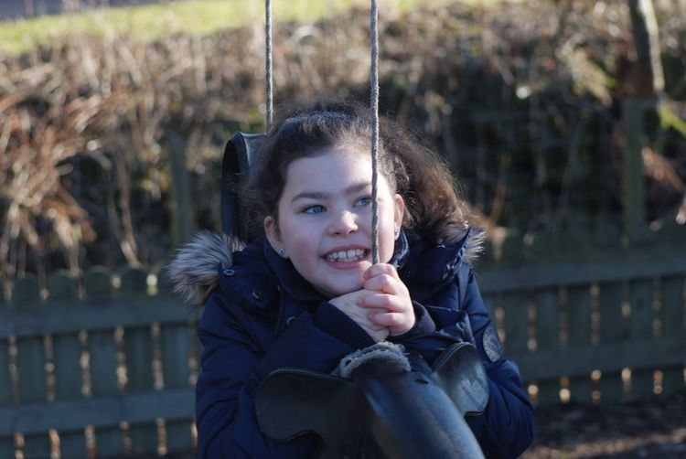 Tire Swing Tyre Swing EyeEm Selects Looking At Camera Leisure Activity One Person Front View Outdoors Portrait Smiling Focus On Foreground Real People Lifestyles Young Adult Young Women Day Happiness Childhood Warm Clothing Nature Close-up People