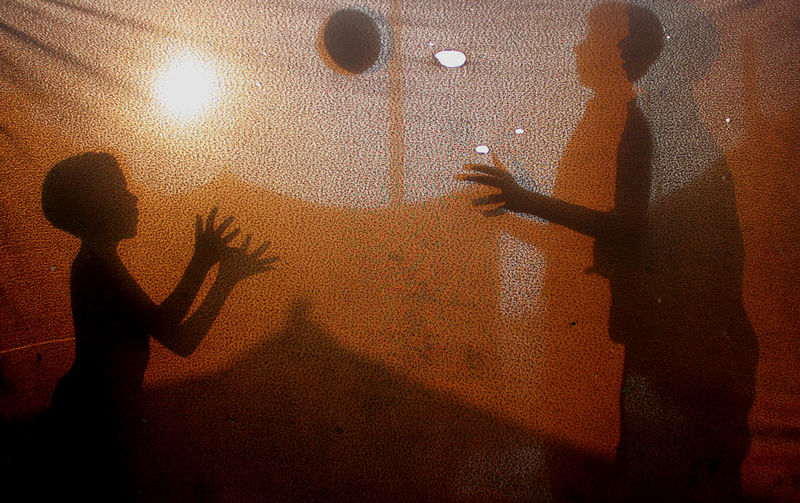 Shadow Of Friends Playing With Ball On Fabric During Sunset