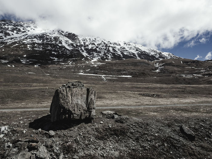 Scenic view of landscape and snowcapped mountains against cloudy sky
