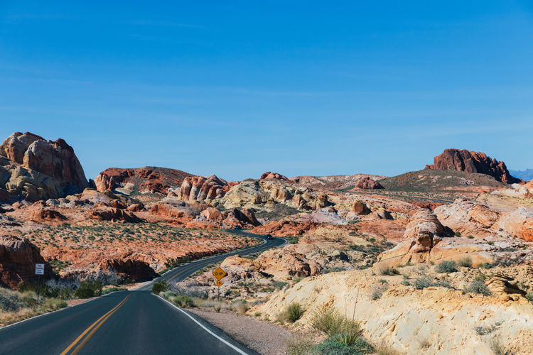 Road by rock formations against blue sky
