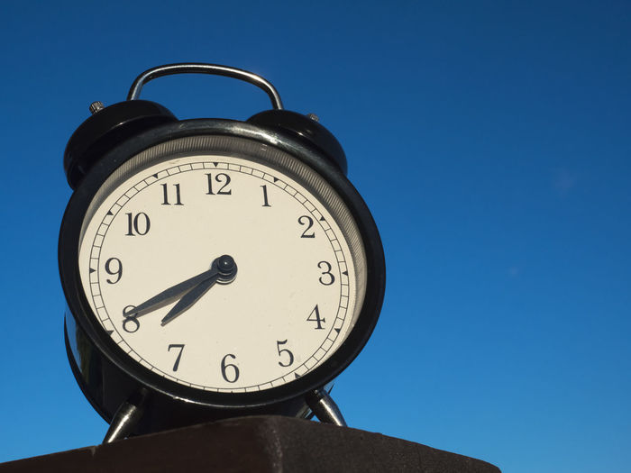 Low angle view of alarm clock against clear blue sky