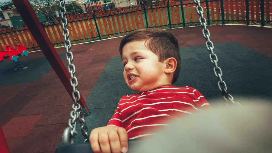 Portrait Of Young Boy On Swing