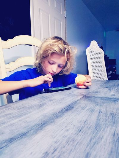 Boy holding apple while using smart phone on table at home