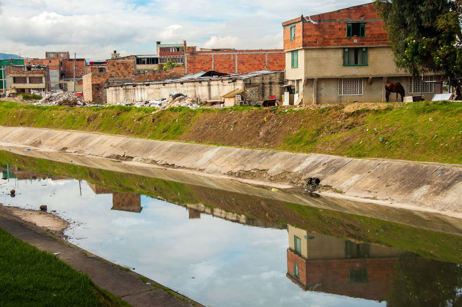 A lower class neighborhood reflected in a river in Bogota, Colombia Bogotá Class Colombia Community Crime Dirt Dirty Drug Garbage Ghetto Homeless House Junk Latin Low Neighborhood Police Poor  River Shack Slum South America Structure Trash Underprivileged