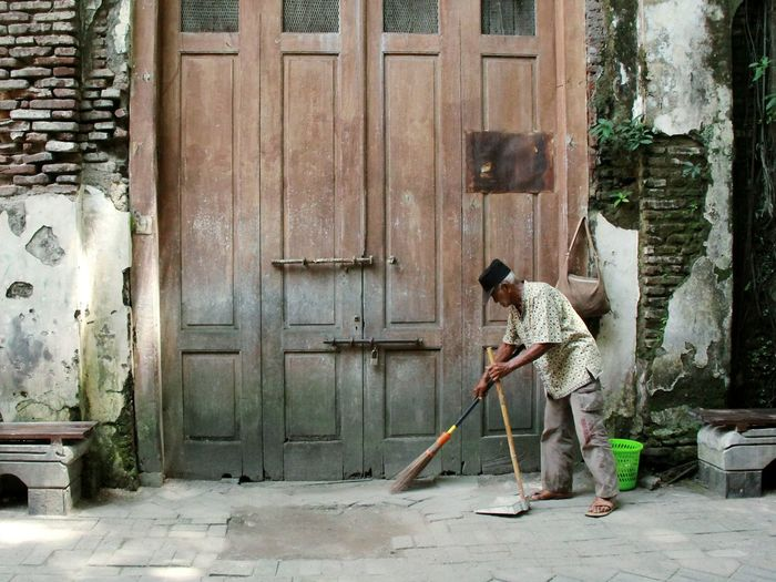 Man sweeping while standing against entrance of building