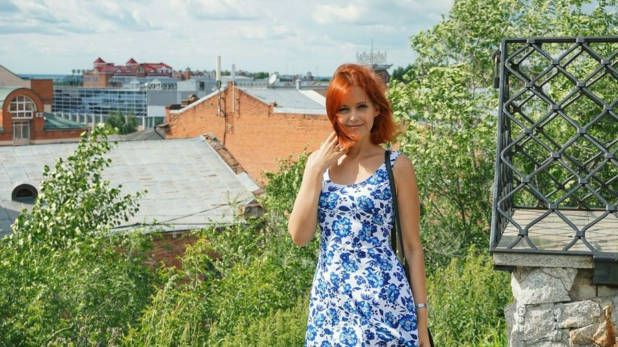 Portrait of redhead woman standing in city