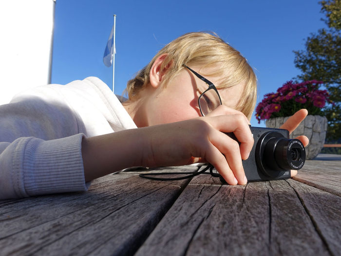 Camera - Photographic Equipment Clear Sky Blond Hair Boy Child Childhood Children Only Close-up Day Education Eyeglasses  Human Hand Leisure Activity Lifestyles One Person Outdoors People Photographing Photography Themes Technology