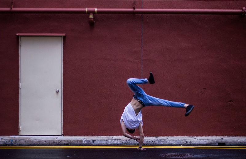 Full Length Of Young Man Doing Cartwheel By Maroon Building