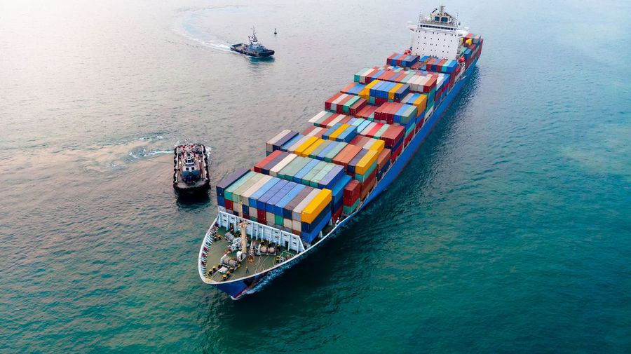 Aerial of cargo ship carrying container and running for export goods from cargo yard port to other