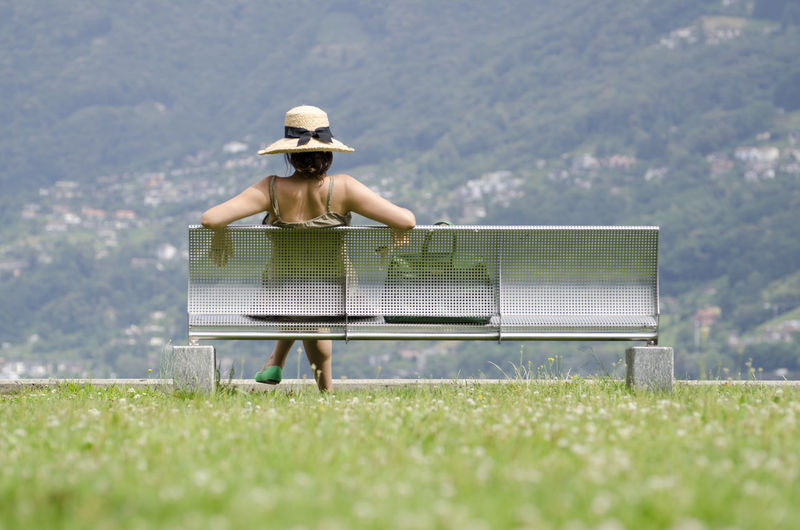 Woman with Straw Hat and Handbag Sitting on a Metal Bench in Ticino, Switzerland. Bench Low Angle View Modern Rear View Sitting Bag Beauty In Nature Color Day Enjoyment Grass Handbag  Hat Lifestyles Metal Nature One Person Outdoors Protection Real People Relaxation Straw Hat Summer Sun Hat Women