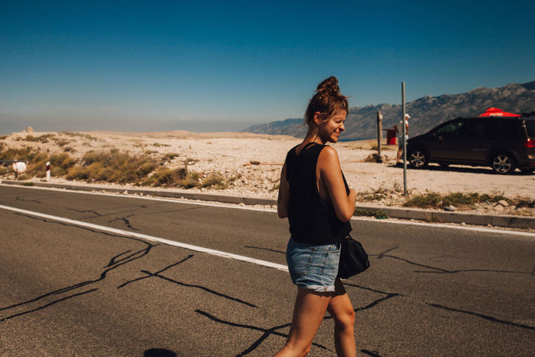 Woman standing on road against sky in city