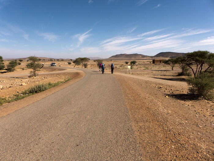 Road through a small desert village in the south of Morocco Morocco Dessert Travel Landscape Dry View The Way Forward Street Road Africa Direction Transportation Diminishing Perspective People Hiking Rear View Arid Climate Climate Real People Lifestyles Full Length Sky Scenics - Nature Cloud - Sky Sand