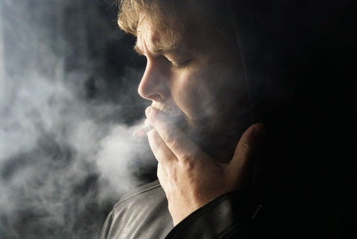 Smoking a cigarette. Low key image with sidelight. Headshot People Close-up One Person Black Background Smoke Smoking Low Key Sidelight SideLightPhotography Only Men One Man Only Night