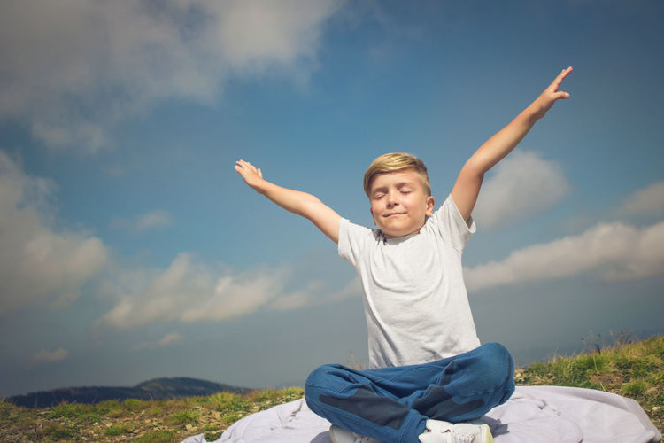 Cute boy sitting with arms outstretched on rock against sky
