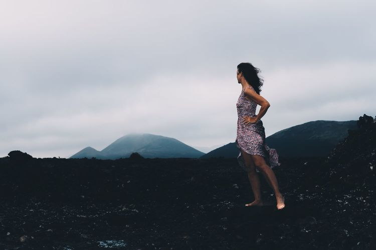 Side view of woman standing on mountain against sky