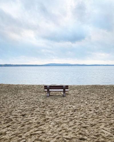 Empty bench on beach against sky