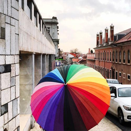 Multi colored umbrella against sky in city
