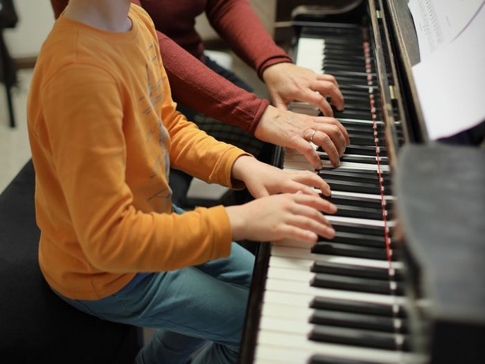 Midsection Of People Playing Piano At Home