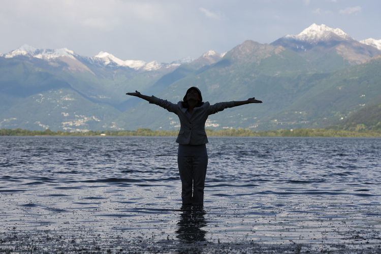 Woman standing in the water with outstretched arms in an alpine lake Maggiore with snow-capped mountain in Ticino, Switzerland. Adult Alpine Lake Arms Outstretched Arms Raised Beauty In Nature Day Freedom Idyllic In The Water Lago Maggiore Landscape Mountain Mountain Range Nature One Person One Woman Only Outdoors Scenics Silhouette Snow-capped Standing Swiss Alps Tranquility Water Woman