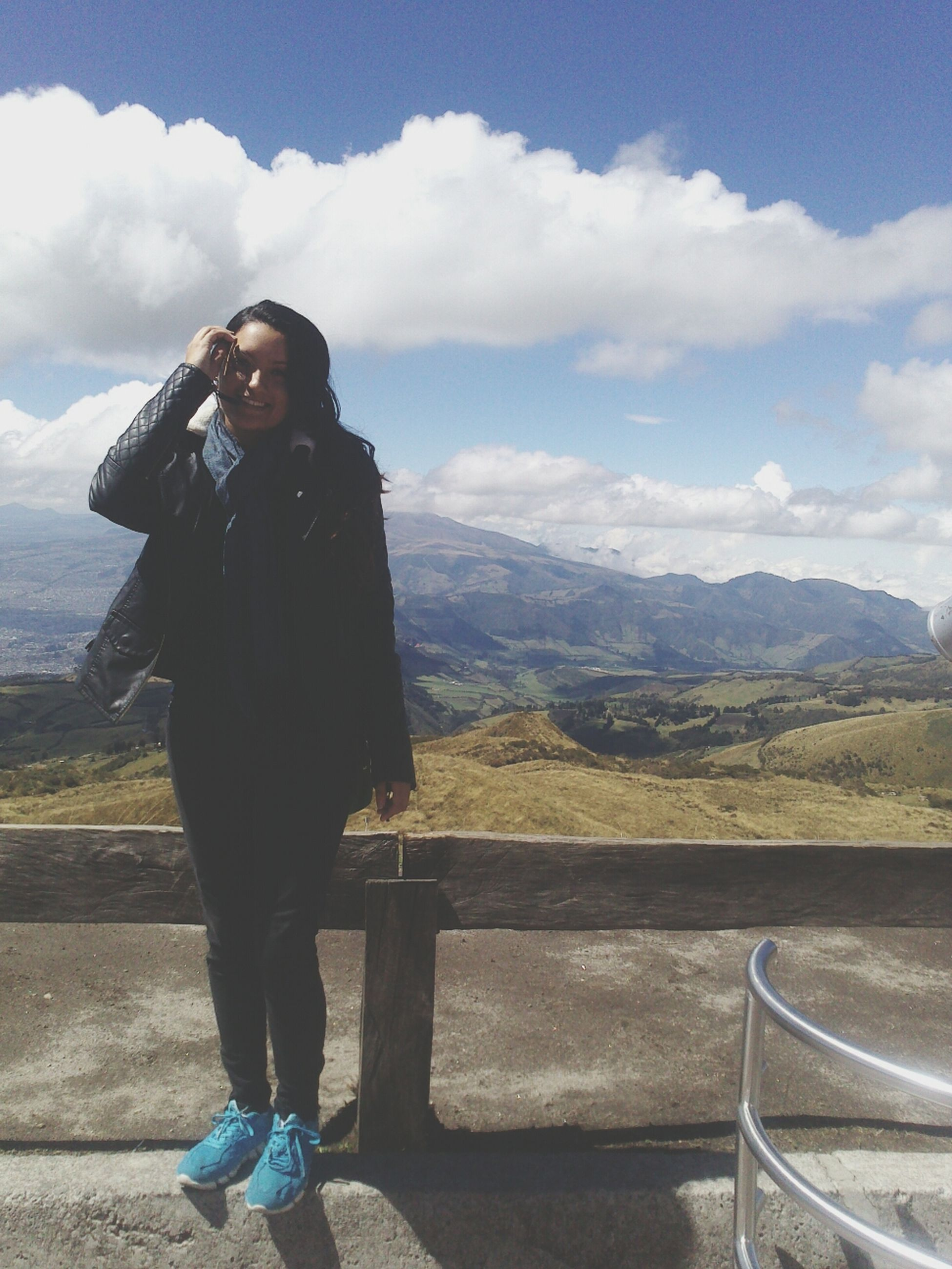 young adult, lifestyles, person, casual clothing, mountain, leisure activity, sky, young women, standing, portrait, looking at camera, mountain range, cloud - sky, full length, three quarter length, smiling, landscape, front view