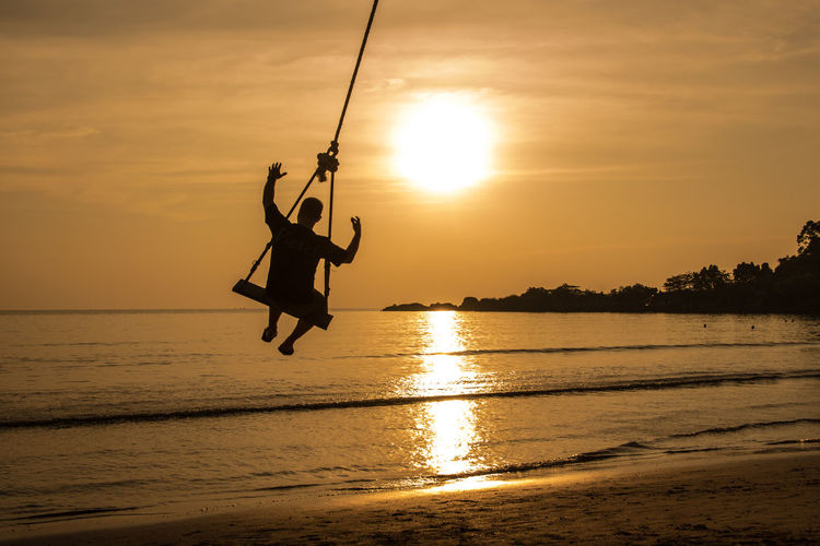 Silhouette person swinging against calm sea at sunset