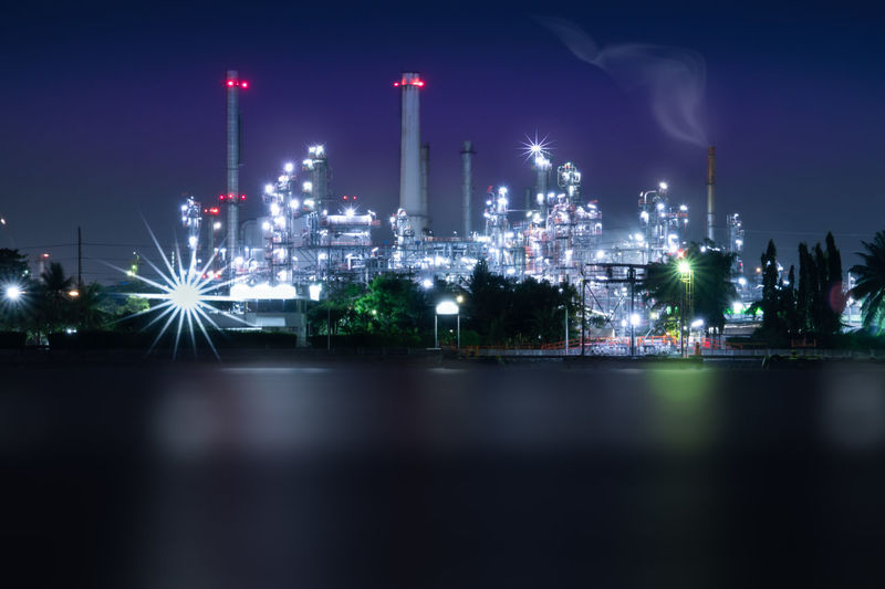 Industrial zone at night . Oil refinery factory operating 365 days a year night scene full lighting smooth water surface with long exposure shot . Air Pollution Architecture Building Exterior Built Structure Chemical Plant Defocused Environment Factory Fuel And Power Generation Illuminated Industrial Zone Industry Lighting Equipment Long Exposure Night Photography Nature Night No People Oil Industry Oil Refinery Pollution Refinery Reflection Sky Smoke Stack Water