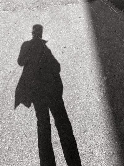 Shadow of man on road