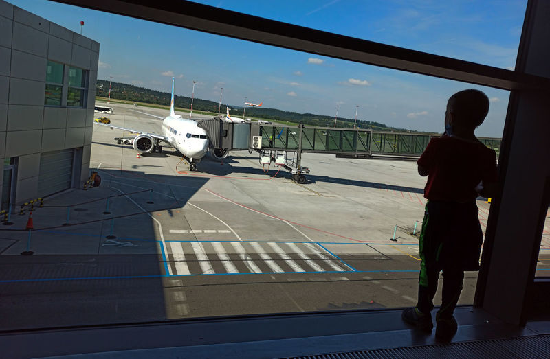 Man standing on airport runway seen through window