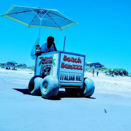 Ice Aqua Beach Blue Cart Clear Sky Day Full Length Leisure Activity Men Nature One Person Outdoors People Protection Real People Safety Sand Sitting Sky Summer Transportation Umbrella Vacations Young Adult