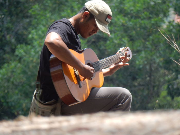 Side view of man sitting with guitar against plants