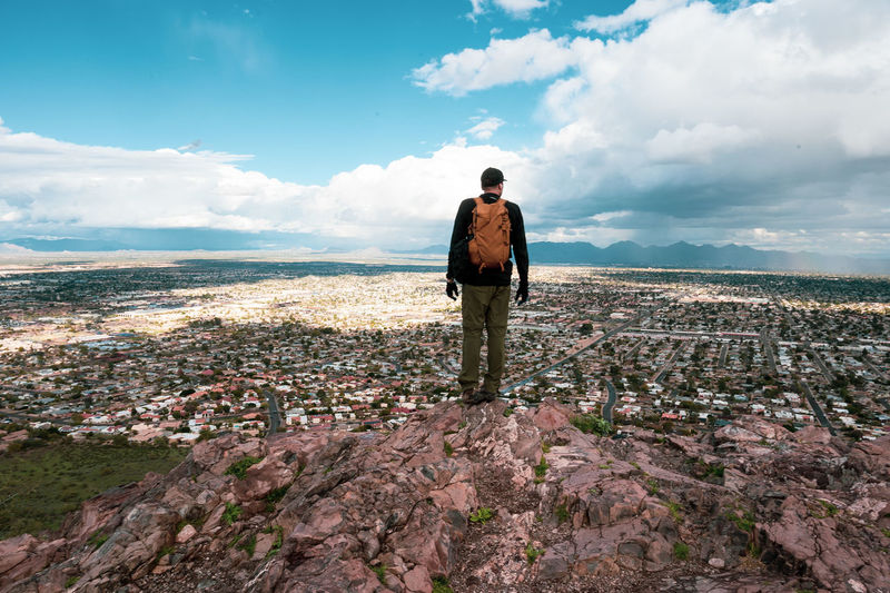 Rear view of male hiker standing on mountain with cityscape in background against cloudy sky